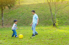 Asian family. Asian father and son outdoor quality time enjoyment, asian people playing during beautiful sunset Royalty Free Stock Photos