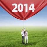 Asian family grabbing new future banner. Portrait of happy family grabbing new future banner in 2014 Stock Photo