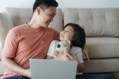 This Asian family has  father and daughter. A little girl and father are looking at laptop they are happy in their home stock photo