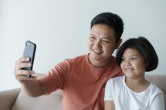 This Asian family has a father and daughter . A little girl   And father  video call they are happy in their home ather. This Asian family has a father and stock image