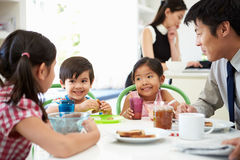 Asian Family Having Breakfast Before Husband Goes To Work Royalty Free Stock Image
