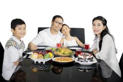 Asian family having dinner together on studio. Picture of Asian family looking at the camera while having dinner together, isolated on white background Stock Images