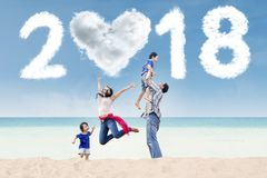 Asian family having fun in the beach. Portrait of Asian family having fun in the beach with clouds shaped heart and numbers 2018 in the sky stock photos