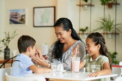 Asian family having fun in cafe. Cheerful Asian women feeding son while sitting at cafe table near smiling girl stock image