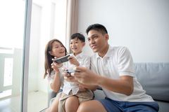 Asian family having fun playing computer console games together, Father and son have the handset controllers and the mother is ch royalty free stock image