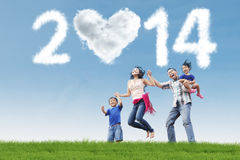 Asian family having fun under cloud of new year 2014. Happy family having fun in the park with heart shaped cloud of new year 2014 Royalty Free Stock Photos