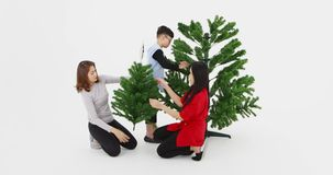 Asian family help to decorate Christmas tree. Asian family help each other to decorated peak of Christmas tree by silver star together, prepare to celebrated stock footage