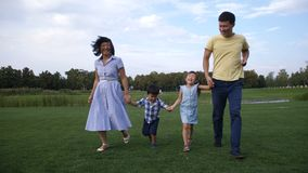 Asian family holding hands and running in park stock video footage