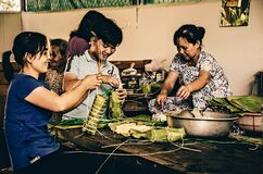 Free Asian Family In The Mekong Delta Preparing Food By Wrapping It In Leaves. (Ho Chi Minh City, Vietnam - 2/01/2020 Stock Image - 183463311