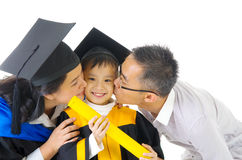 Asian family. Asian kindergarten child in graduation gown and mortarboard kissed by her parent during graduation Stock Images