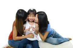 Asian family kissing little girl stock photography