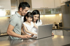 Asian Family in the kitchen with a laptop. Asian Family watching something on the computer, in the kitchen Stock Photo