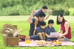 Asian family with a laptop in the park. Image of Asian family using a laptop while enjoying holiday and picnicking in the park Royalty Free Stock Images