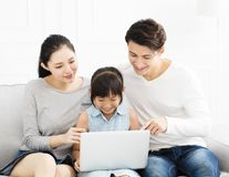 Asian family with laptop on sofa Stock Images