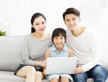 Asian family with laptop on sofa. Happy asian family with laptop on sofa Royalty Free Stock Photography