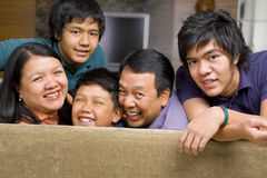 Asian family lifestyle portrait. Happy Asian family in the living room gazing to camera royalty free stock images