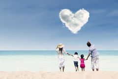 Asian family looking at heart cloud at beach. Happy family running towards the beach under love cloud Royalty Free Stock Photos