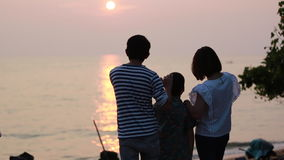 Asian family looking sunset with sea background.  stock footage