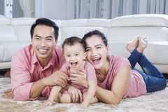 Asian family lying on floor. Portrait of asian family lying on the floor while laughing together in living room Stock Photography