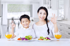Boy and mom are happy with the salad. Asian family are making OK gesture while having salad at home Stock Image