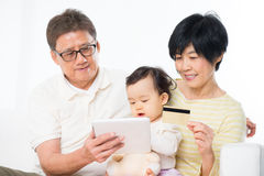 Asian family online shopping. Indoor, grandparents and grandchild living lifestyle at home Stock Image