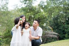 Family blowing soap bubbles outdoors. Asian family outdoors activity. Parents and children blowing soap bubbles at garden park stock images