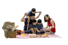 Asian family picnicking with a laptop. Image of Asian family using a laptop while enjoying holiday and picnicking in the studio,  on white background Royalty Free Stock Image