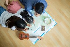 Asian family is planning a travel trip. They`re looking at a world map royalty free stock photography