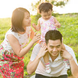 Asian family playing at outdoor park during sunset Stock Photo