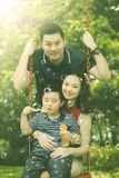 Asian family playing with soap bubbles in park. Portrait of Asian family smiling at the camera while playing with soap bubbles in the park Stock Photography