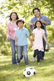 Asian family playing soccer in park Royalty Free Stock Photo
