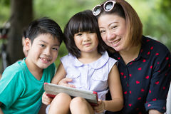 Asian family are playing together with a computer tablet in the. Park, Bangkok Thailand Royalty Free Stock Photography