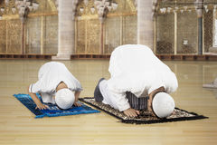 Asian family praying in the mosque. Picture of Asian family wearing Islamic clothes while posing prostration in the mosque stock images