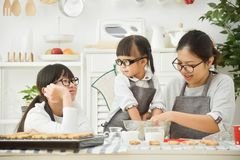 Asian family preparing the dough bake. Happy Asian family preparing the dough bake for cookies and cakes in the kitchen stock photography