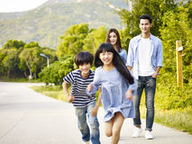 Asian family relaxing in park. Two asian children running in park while their parents watching affectionately Royalty Free Stock Photos