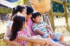Asian Family Resting By Fence With Old Fashioned Cycle. Happy Asian Family Resting By Fence With Old Fashioned Cycle In Countryside Royalty Free Stock Image