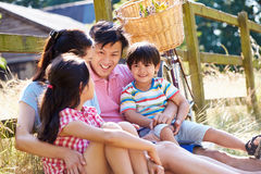 Asian Family Resting By Fence With Old Fashioned Cycle. Smiling At Each Other royalty free stock photos