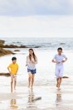 Asian family running on sand beach in cloudy day Stock Photos