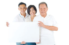 Asian family. Senior men with his son and daughter. Happy Asian family senior father and adults offspring holding a blank white sign on isolated background royalty free stock photography