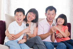 Asian family singing karaoke. Family at home. Portrait of a happy Asian family singing karaoke through microphone in the living room Stock Photo