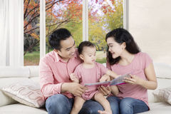 Asian family sitting on couch with a book Royalty Free Stock Image