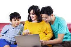 Asian family sitting on couch with laptop Royalty Free Stock Image