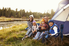 Asian family sitting outside their tent, looking to camera Royalty Free Stock Image