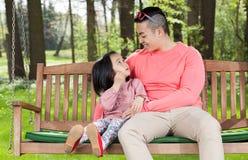 Asian family sitting on a swing. Horizontal Royalty Free Stock Photo