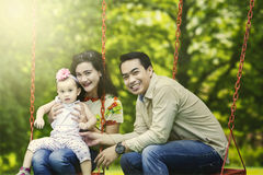 Asian family sitting on the swing Stock Image
