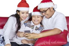 Asian family with smartphone and Santa hat Royalty Free Stock Photo
