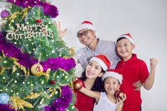 Asian family celebrating Christmas on studio. Asian family smiling at the camera near a Christmas tree while celebrating Christmas in the studio Stock Photo