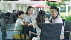 Asian Family Smiling, Eating & Drinking Outdoor At Streetside Table Stock Photo