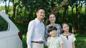 Asian family standing beside car looking forward and smiling stock photo