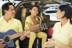 Family singing and playing guitar. Asian family standing near his car outdoors and spending funny time together mother with little daughter singing a song while royalty free stock photo